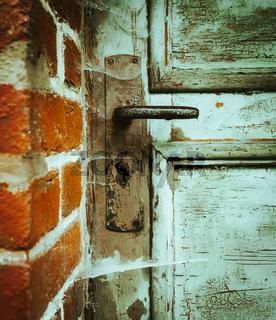 Old ramshackle wooden door with cobwebs
