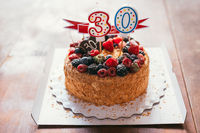 raspberries blackberry birthday cake with candles number 30 on defocused background with wooden table. Selective focus macro shot with shallow DOF
