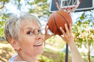 Seniorin als sportlicher Rentner beim Basketball