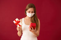 Girl with face mask opening present on valentines day