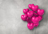 Pink heart shape air balloons group on a concrete wall banner