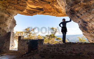 Woman looking out to mountain views from a cave