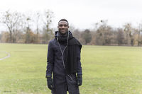 Young Black Man Posing on Park Grass in Autumn