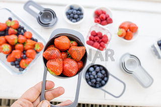 Female hand holding measuring cup full of strawberries above more berries