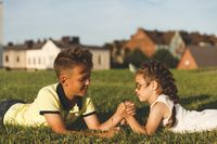 young brother and sister lying on the grass wrestle in their arms