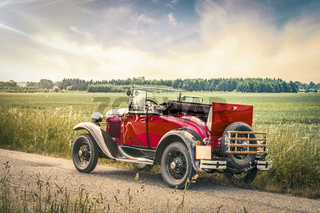 Antique red car on a road in a countryside landscape