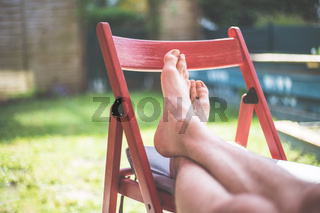 Lazy time at home in the own garden. Resting feet and legs on a red chair.