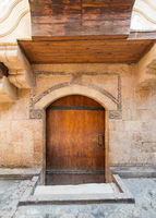 Exterior of aged stone house with weathered walls and arched wooden door, in old district