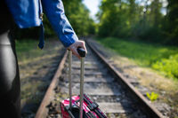 A close-up view of a teenage girl holding a pink travel bag by a retractable plastic handle while walking along the railroad tracks.