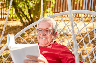 Senior Mann beim Buch lesen im Garten