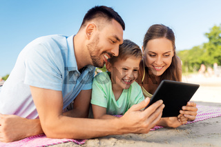 happy family with tablet computer on summer beach