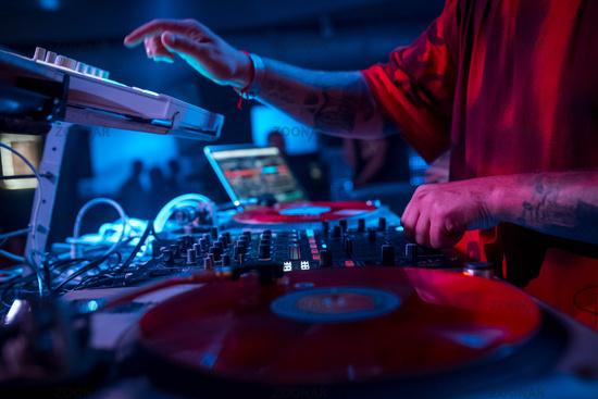 DJ in a red T-shirt blurting behind a dj keyboard
