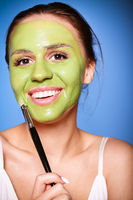 Cheerful woman applying green mask