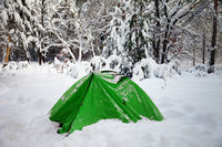 Green camping tent in snow at snowy winter forest
