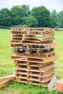 High pile of wooden pallets in meadow