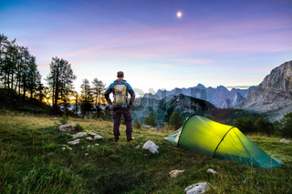 Hiker with Backpack standing on Mountain and Tent glowing under a moon night sky at sunset or sunrise twilight hour. Alps, Sleme, Triglav National Park, Slovenia.