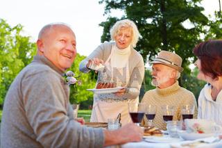 Frau serviert Gugelhupf an Senioren