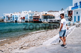 young guy on vacation at the Greek Island of Mykonos, men relaxing at the little venice village of Mykonos Island