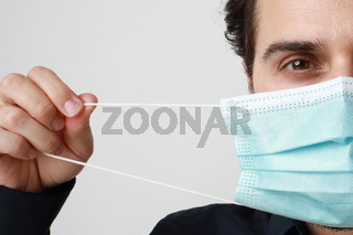 Cropped portrait of young man in medical mask, stands on light background. Pandemic situation, Covid-19.