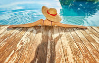 Woman in hat relaxing at pool