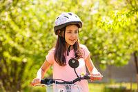 8-years girl in biking helmet on outside ride
