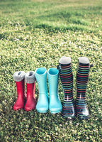 Colorful rubber boots on green grass