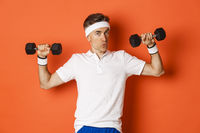Concept of workout, gym and lifestyle. Image of healthy and strong middle-aged fitness guy, doing sport exercises with dumbbells, standing over orange background