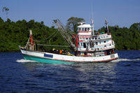 Fishing vessel underway at sea over blue sky and sea.