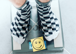 close-up of person in socks on bathroom scale with smiley face