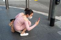 Singapur, Republik Singapur, Frau mit Mundschutz fotografiert an einer Ampel