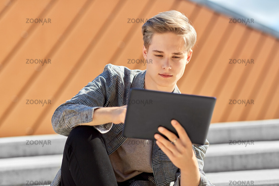 young manor teenage boy with tablet pc in city