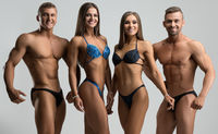 Muscular fitness models shot against gray wall