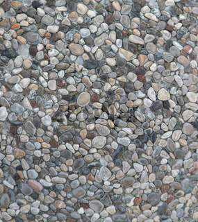 Multi-colored sea pebbles at pathway outdoors. Small round stones are in cement mortar. Selective focus at centre of image. Abstract texture or background