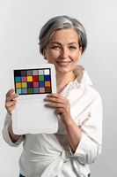 Mature woman holds color checker smiling at camera. Gray haired woman in white blouse shows target for color adjustment. Isolated on white background