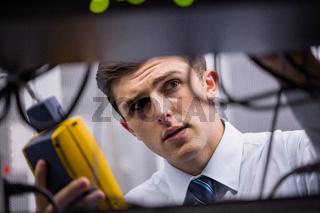 Technician using digital cable analyzer on server
