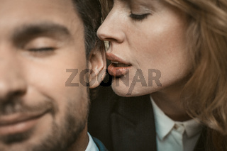 Woman kisses or whispers in man's ear. Selective focus on female lips near male ear in the center of image. Passionate couple in love. Close up shot