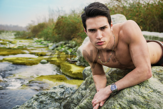 Handsome fit shirtless young man laying on rock