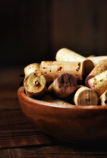 Closeup of a wooden bowl full of used wine corks. Vertical with strong side light and copy space.