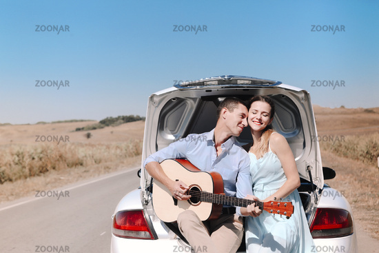 Romantic couple with guitar resting near car