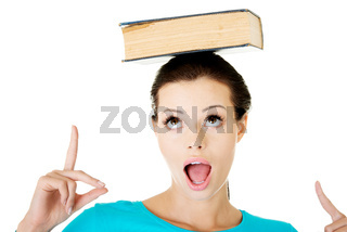 Beautiful young woman with book on her head.