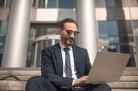 Successful businessman works on laptop sitting on steps of business center. Smiling man wearing business suit and sunglasses. High quality photo