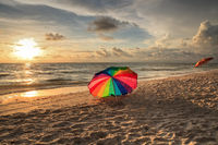 Rainbow umbrella on White sand at Delnor Wiggins State Park at sunset