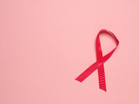 Pink ribbon curl on a pink paper background ,symbol for Liver Cancer awareness, World Cancer Day