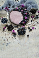 Sweet and tasty tart with fresh blueberries, blackberries and grapes, served on stone background
