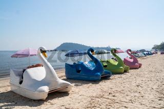 A row of colored swan paddle boats on the sand at Ilha de Paqueta Island in Rio de Janeiro.