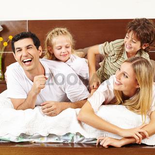 Kinder kitzeln Eltern im Bett
