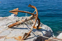 Old rusty anchor on rock by blue sea