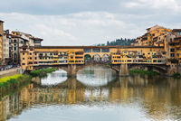 FLORNCE, ITALY - APRIL 24, 2019: Ponte Vecchio. View of the historic buildings in Florence. Reflection in the river