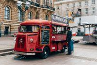 Unidentified man is buying flammkuchen or tarte flambee in a food truck in Hamburg