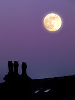 a glowing full moon in a purple twilight summer sky above a house rooftop in silhouette
